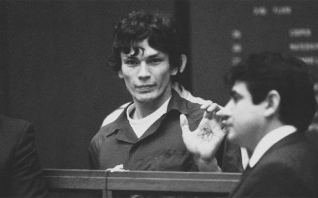 Richard Ramirez, center, know as the Night Stalker, shown in custody with pentagram on palm in this undated photo. The man on the right is unidentified. Ramirez died of natural causes in state prison, California Department of Corrections officials said.