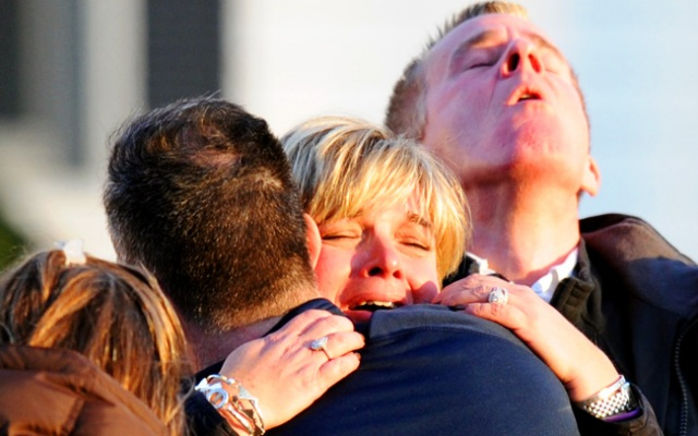 People embrace on December 14, 2012 in the aftermath of a shooting at Sandy Hook Elementary school that left 26 people dead, including 20 children and the gunman, identified as 20-year-old Adam Lanza. The gunman also killed his mother, who was found dead at her home. Click to see photos from Sandy Hook.