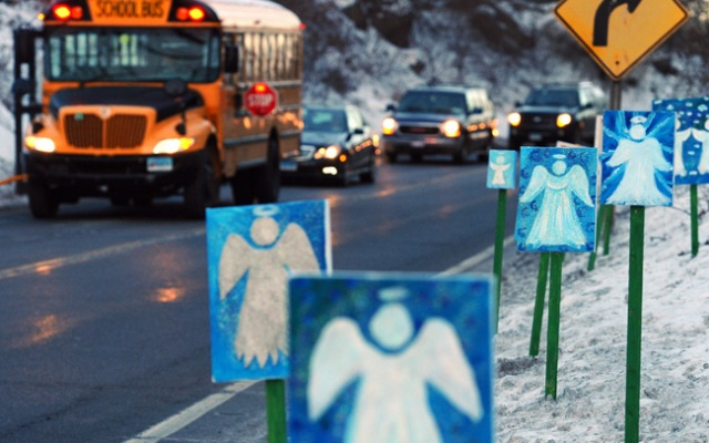 A bus traveling from Newtown, Conn., to Monroe stops in front of 26 angels along the roadside on the first day of classes for Sandy Hook Elementary School students after the Dec. 14 shooting, in Monroe, Conn., Thursday, Jan. 3, 2013.