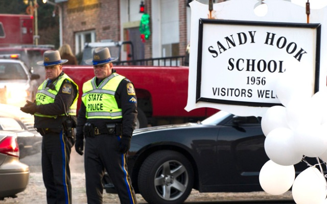 Police stand guard at the entrance to the Sandy School on December 15, 2012 in Newtown, Connecticut. The residents of an idyllic Connecticut town were reeling in horror from the massacre of 20 small children and six adults in one of the worst school shootings in US history. The heavily armed gunman shot dead 18 children inside Sandy Hook Elementary School, said Connecticut State Police spokesman Lieutenant Paul Vance. Two more died of their wounds in hospital.     AFP PHOTO/DON EMMERT