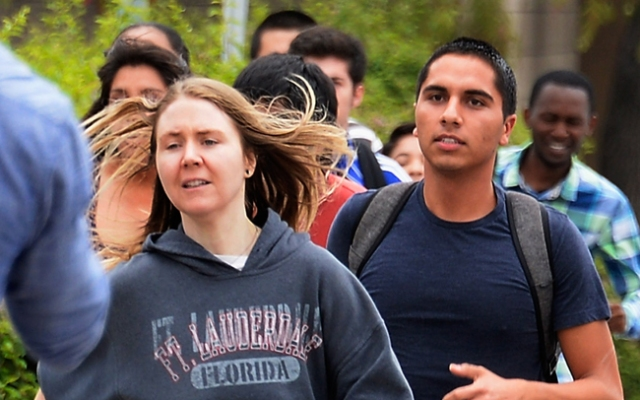 Students rush to safety after shots were fired near the Santa Monica College. An armed gunman opened fire on a bus, a home and cars near the college on Friday afternoon. Police confirmed there are multiple victims and a potential suspect is in custody. Click to see more dramatic photos from the scene.