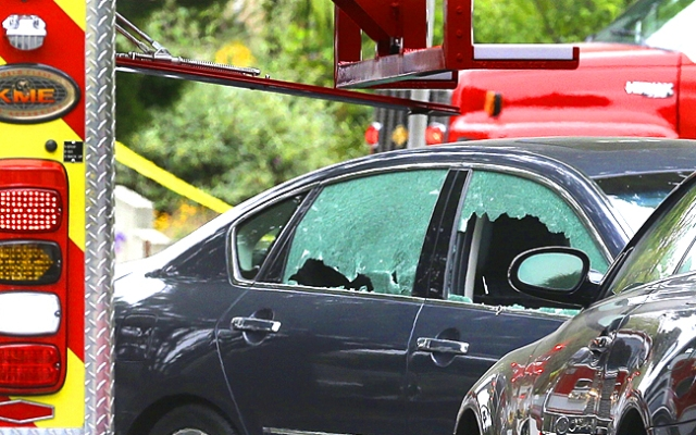 A car with its windows broken stands near where shots were fired near Santa Monica College Friday, June 7, 2013. Police say they plan to release new details in the fatal shooting spree Thursday evening.