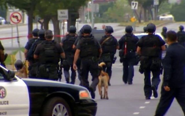 Officers search for a gunman who opened fire Tuesday June 25, 2013 on two detectives in the Mid-City area.