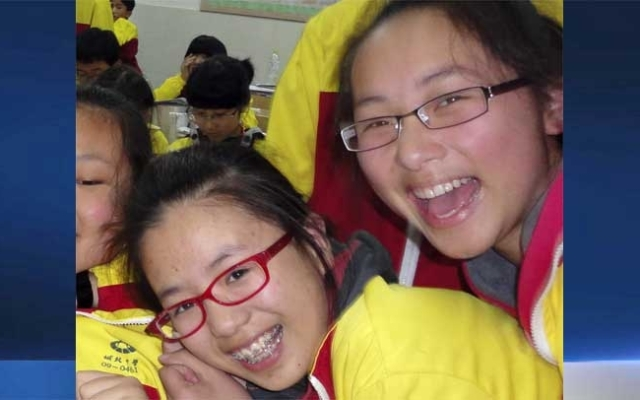 In this undated photo made available Monday, July 8, 2013, Ye Meng Yuan, left, and Wang Linjia, right, pose for photos with other classmates in the classroom in Jiangshan city in eastern China's Zhejiang province. Chinese state media and Asiana Airlines have identified the two victims of the Asiana Airlines crash at San Francisco International Airport girls as Ye Mengyuan and Wang Linjia, students in Zhejiang, an affluent coastal province in eastern China.