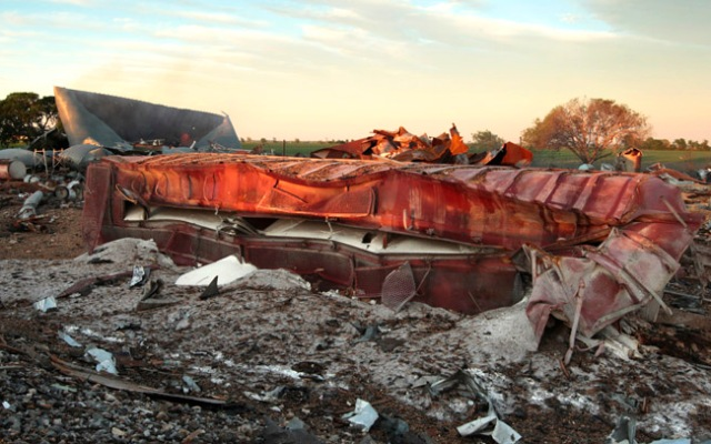 A railroad boxcar filled with ammonium nitrate lays on its side near to the remains of the fertilizer plant that exploded yesterday afternoon on April 18, 2013 in West, Texas. According to West Mayor Tommy Muska, around 14 people, including 10 first responders, were killed and more than 150 people were injured when the fertilizer company caught fire and exploded, leaving damaged buildings for blocks in every direction. (Photo by Erich Schlegel/Getty Images)