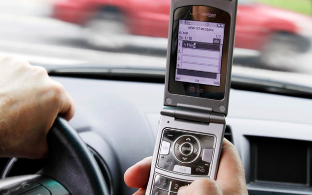 FILE - In this Sept. 20, 2011 file photo, a phone is held in a car in Brunswick, Maine. Texting while driving increased 50 percent last year and two out of 10 drivers say they've sent text messages or emails while behind the wheel despite a rush by states to ban the practice, the National Traffic Safety Administration said Thursday.  (AP Photo/Pat Wellenbach, File)