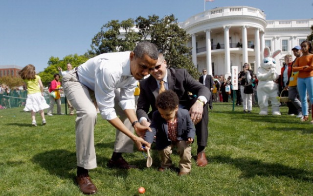 President Barack Obama helps a young participant roll an egg during the White House Easter Egg Roll on the South Lawn, April 9, 2012.