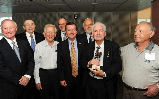 Ed Royce Sr. (holding award) was honored Monday, July 1, 2013, for helping liberate prisoners from a Nazi concentration camp in 1945.
