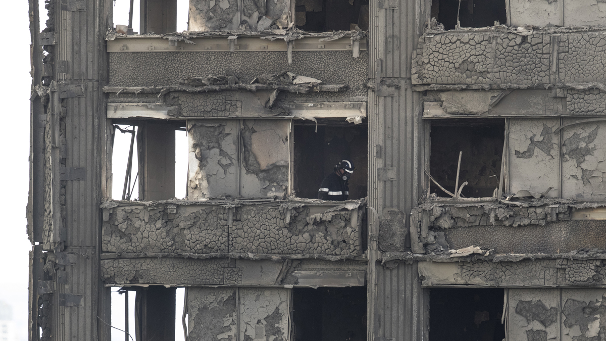 Firefighters inspect the blackened interior of Grenfell Tower on Thursday, June 15, 2017, in London. At least 17 people have been confirmed dead and dozens are missing after the 24-story high-rise was engulfed in flames early Wednesday. The number of fatalities is expected to rise.
