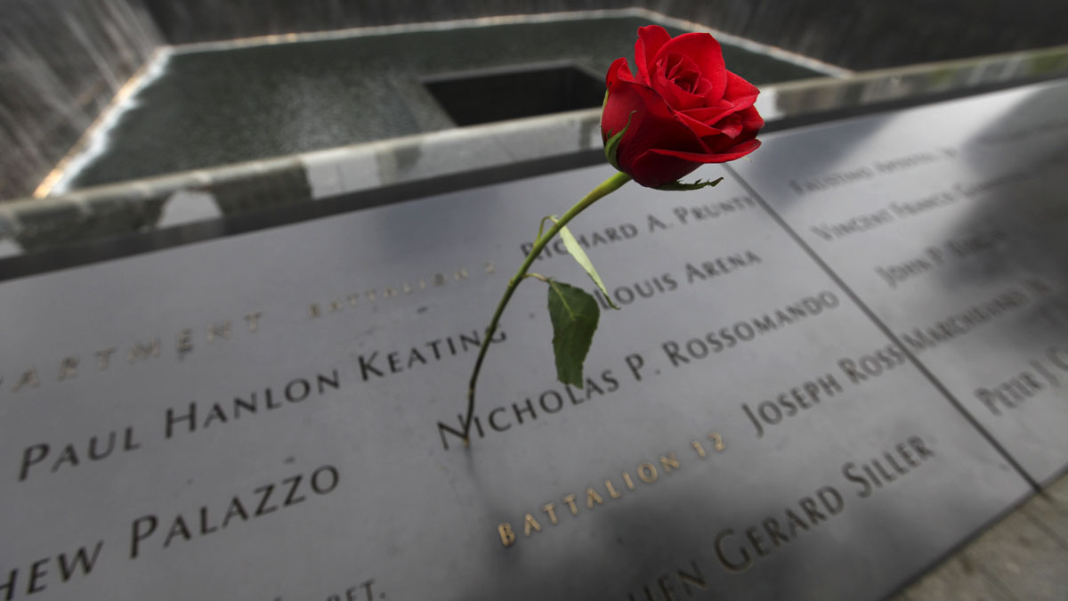 A rose is placed on a name engraved along the South reflecting pool at the Ground Zero memorial site during the dedication ceremony of the National September 11 Memorial Museum in New York on Thursday, May 15, 2014.  (AP Photo/Allan Tannenbaum, Pool)