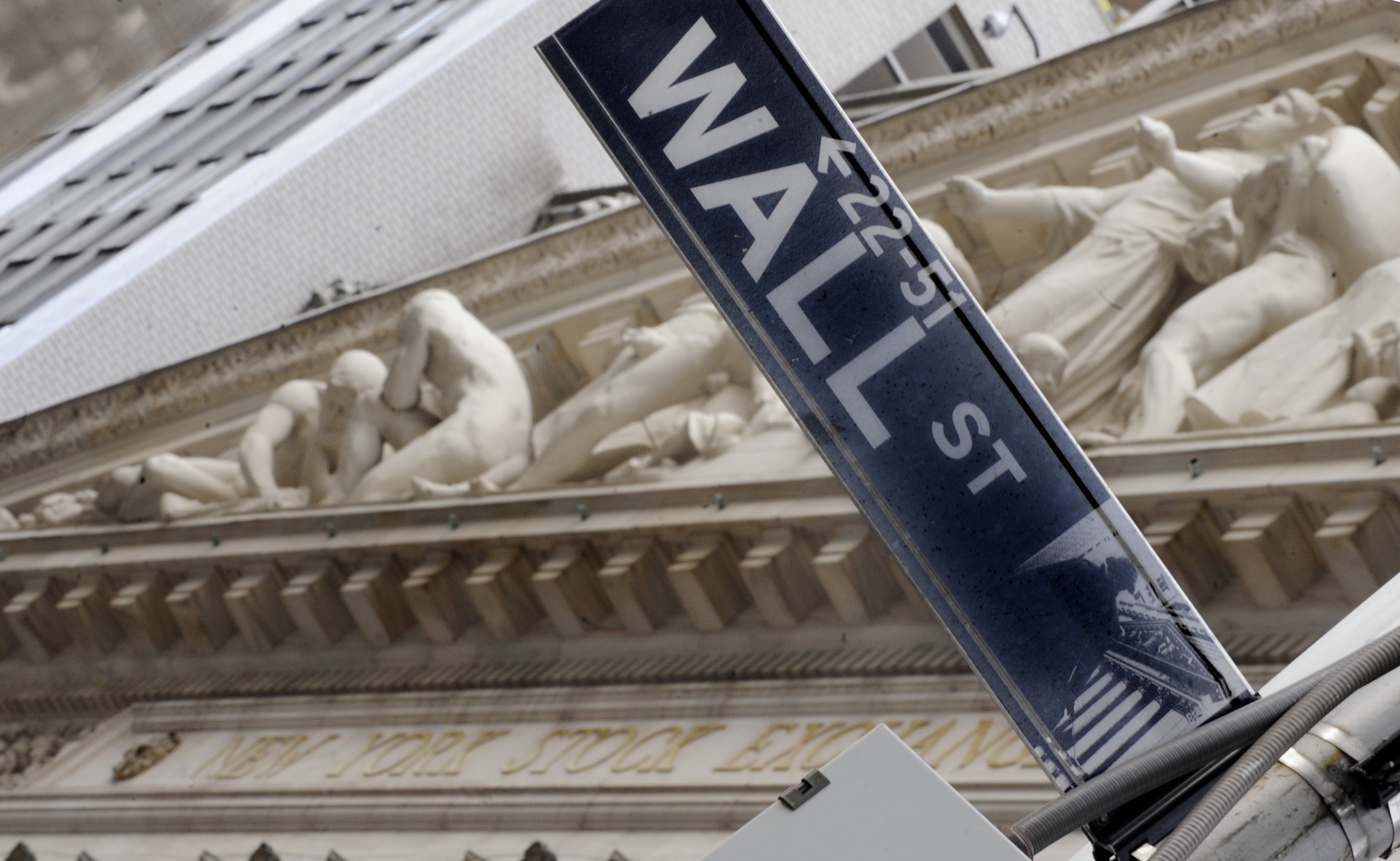 The Wall Street sign is juxtaposed against the sculpture on the facade of the New York Stock Exchange.