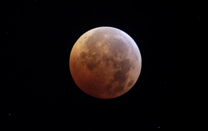 The moon is seen during a total lunar eclipse from New York, Tuesday, Dec. 21, 2010. A total lunar eclipse occurs when the Earth casts its shadow on the full moon, blocking the sun's rays that otherwise reflect off the moon's surface. Some indirect sunlight still pierces through to give the moon its red hue.