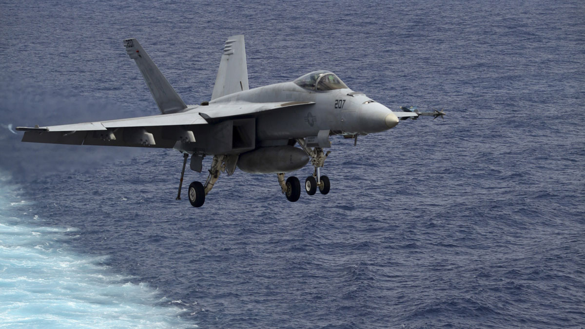 In this photo taken Saturday, Aug. 13, 2011, a U.S. Navy fighter/attack aircraft F/A-18E Super Hornet approaches to land on the deck of the USS George Washington (CVN-73), off southern coast of Vietnam in South China Sea. Less than a week after China launched its first aircraft carrier, the U.S. showed off its own big-boy supercarrier to former enemy Vietnam, one of several smaller Asian nations with jittery nerves amid Beijing's burgeoning maritime ambitions. (AP Photo/Na Son Nguyen)