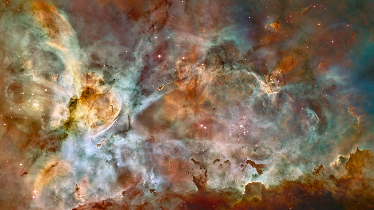 This false-color image made by the NASA/ESA Hubble Space Telescope shows the Carina Nebula. Outflowing winds and intense ultraviolet radiation from the large stars shape the material that is the last vestige of the giant cloud from which the stars were born.