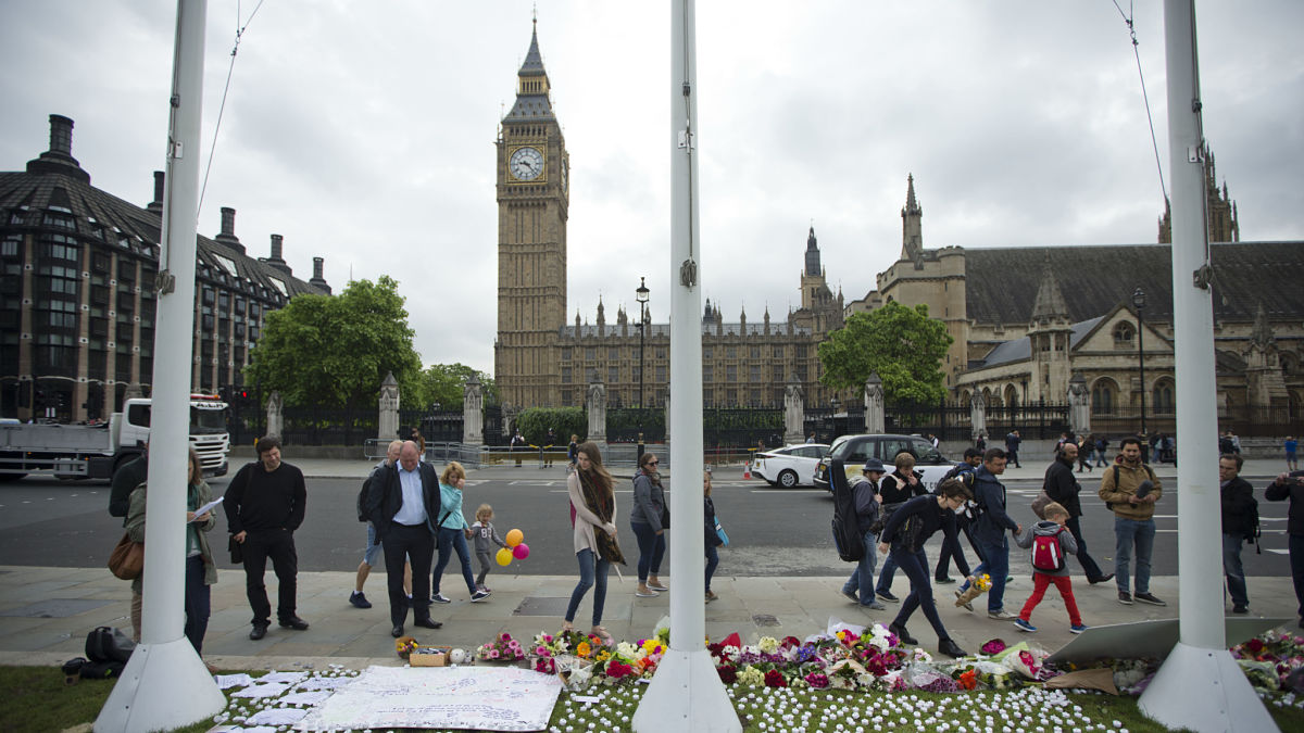 People look at and place tributes for Jo Cox, the 41-year-old British Member of Parliament shot to death in northern England, on Parliament Square outside the House of Parliament in London, on June 17, 2016.