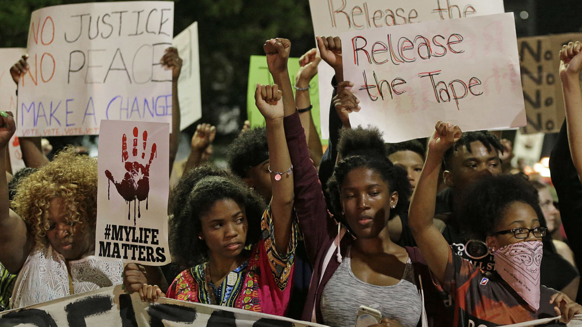 Protesters raise their fists as they march in the streets of Charlotte, N.C. Sept. 23, 2016, over the fatal police shooting of Keith Lamont Scott.