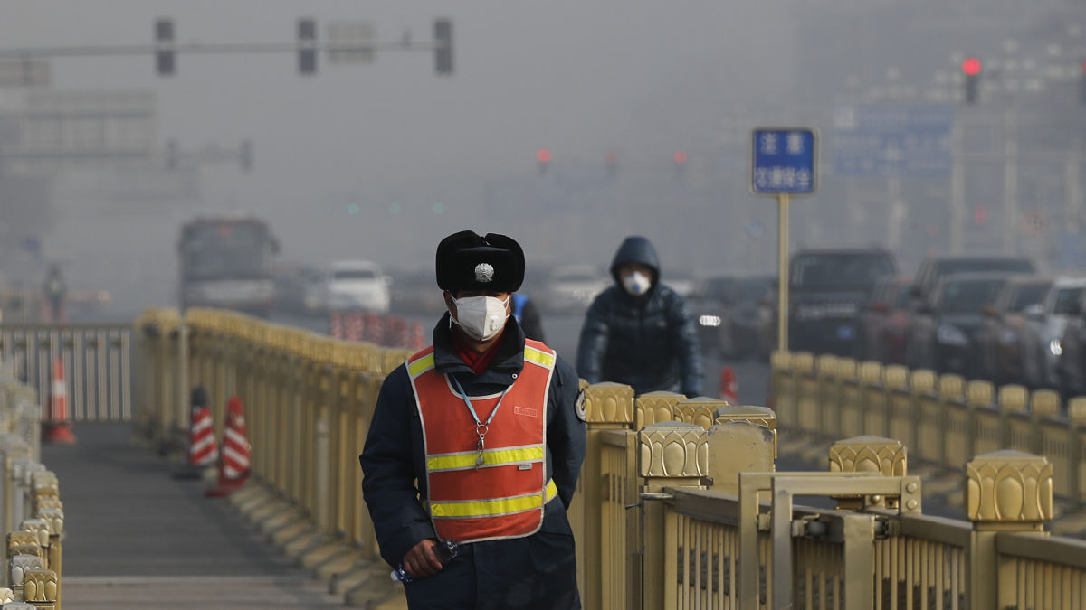 A traffic warden wearing a protection mask walks on a street near Tiananmen Square in Beijing as the capital of China is blanketed by heavy smog on Wednesday, Jan. 4, 2017. China has long faced some of the worst air pollution in the world, blamed on its reliance of coal for energy and factory production, as well as a surplus of older, less efficient cars on its roads. Inadequate controls on industry and lax enforcement of standards have worsened the pollution problem. (AP Photo/Andy Wong)