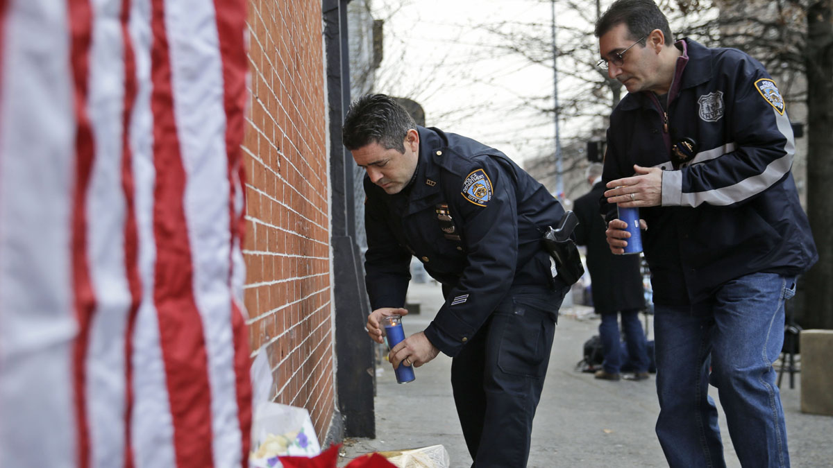 Police officers bring candles to an impromptu memorial near the site where two police officers were killed in the Brooklyn borough of New York, Sunday, Dec. 21, 2014. Police say Ismaaiyl Brinsley ambushed officers Rafael Ramos and Wenjian Liu in their patrol car in broad daylight Saturday, fatally shooting them before killing himself inside a subway station. (AP Photo/Seth Wenig)