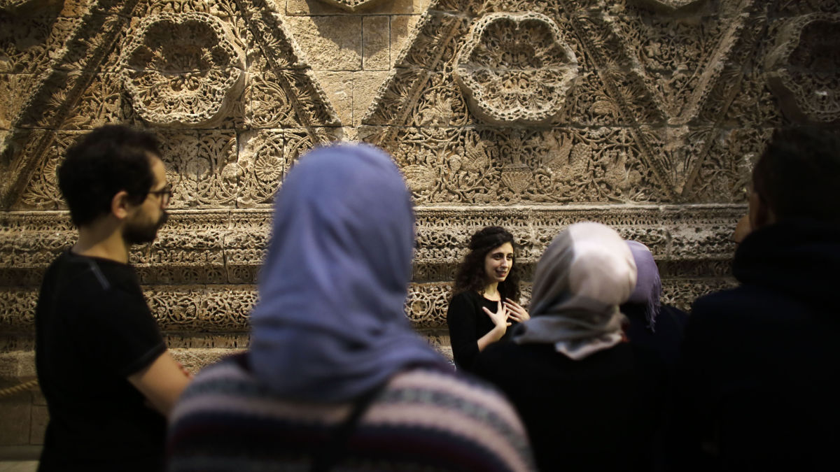 In this Dec. 16, 2015 photo, Zoya Masoud, center, guides a group of refugees on a special tour through the Museum for Islamic Art, at the Pergamon museum in Berlin. In the background is the facade of Mshatta, an ancient Caliph's Palace.  Refugees from Iraq and Syria are being trained as guides to lead other migrants around some of Berlin's most popular museums where they will learn about post-war German history and ancient civilizations. The tours are an opportunity for the migrants to understand how their new home rose from the ashes of WWII and see how their own Islamic culture is appreciated in Germany.  Among the 19 trainee guides is Zoya Masoud, a  Syrian architect who came to Germany four years ago. (AP Photo/Markus Schreiber)