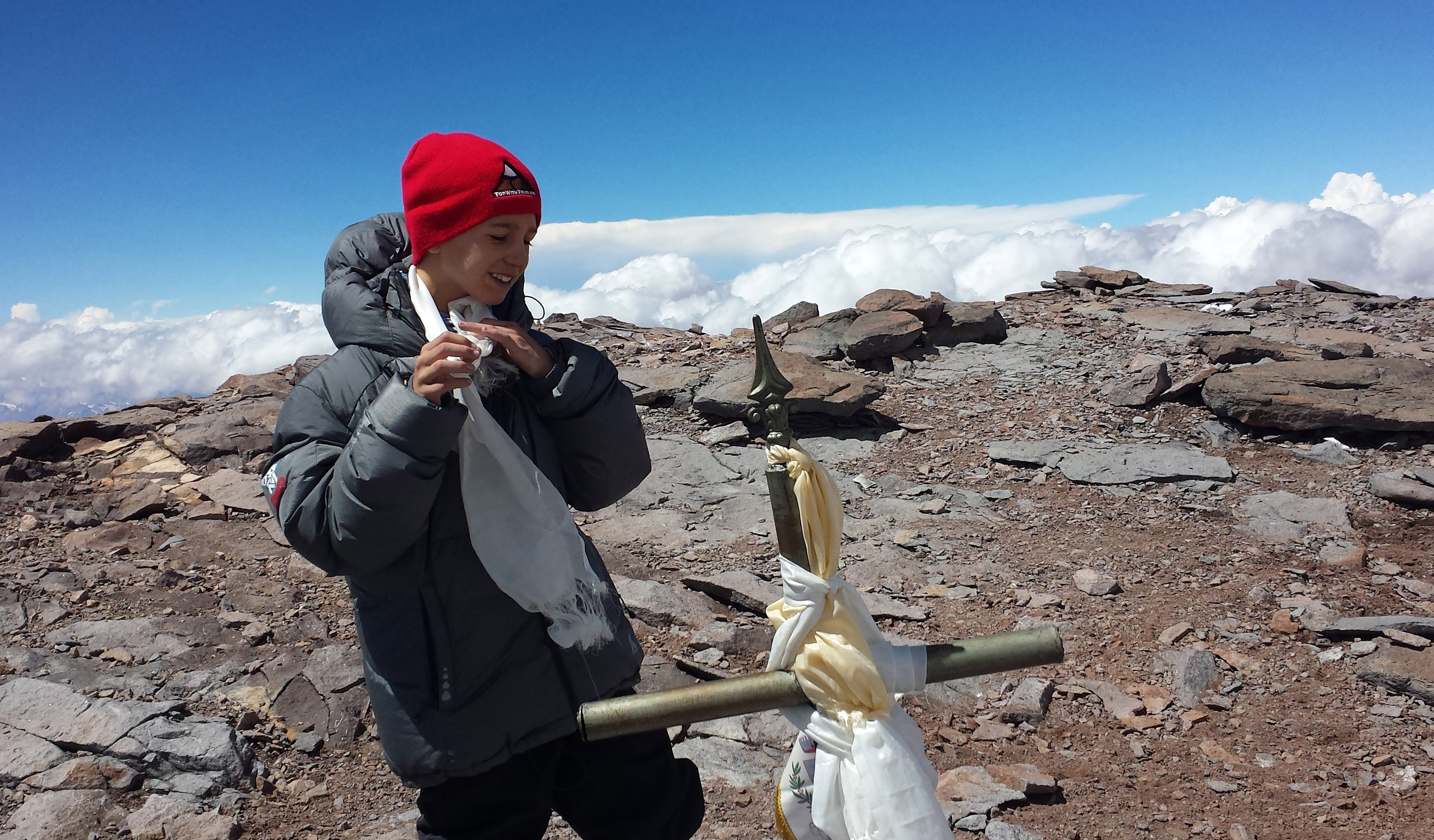 This Dec. 24, 2013 photo released by Lhawang Dhondup shows Tyler Armstrong, from Southern California, standing by a cross on the summit of Aconcagua Mountain in Argentina. The 9-year-old boy has become the youngest person in recorded history to reach the summit of Argentina's Aconcagua mountain, the tallest peak in the Western and Southern hemispheres. (AP Photo/Lhawang Dhondup)
