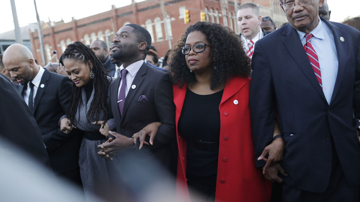 Oprah Winfrey locks arms with David Oyelowo, left, who portrays Martin Luther King Jr. in the movie