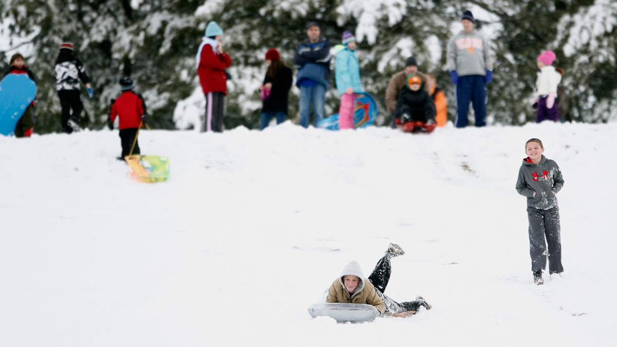 A kid sleds down a hill while others wait their turn on Thursday, Feb. 13, 2014.