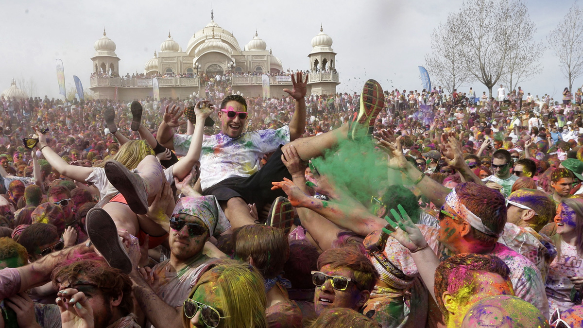 Revelers covered in colored corn starch celebrate during the 2014 Festival of Colors, Holi Celebration at the Krishna Temple Saturday in Spanish Fork, Utah. Nearly 70,000 people are expected to gather starting Saturday at a Sri Sri Radha Krishna Temple in Spanish Fork for the annual two-day festival of colors. Revelers gyrate to music and partake in yoga during the all-day festival, throwing colored corn starch in the air once every hour. The Salt Lake Tribune reports that the large majority of participants are not Hindus, but Mormons. Thousands of students from nearby Brigham Young University come to take part in a festival that is drug and alcohol free. The event stems from a Hindu tradition celebrating the end of winter and the triumph of good over evil.