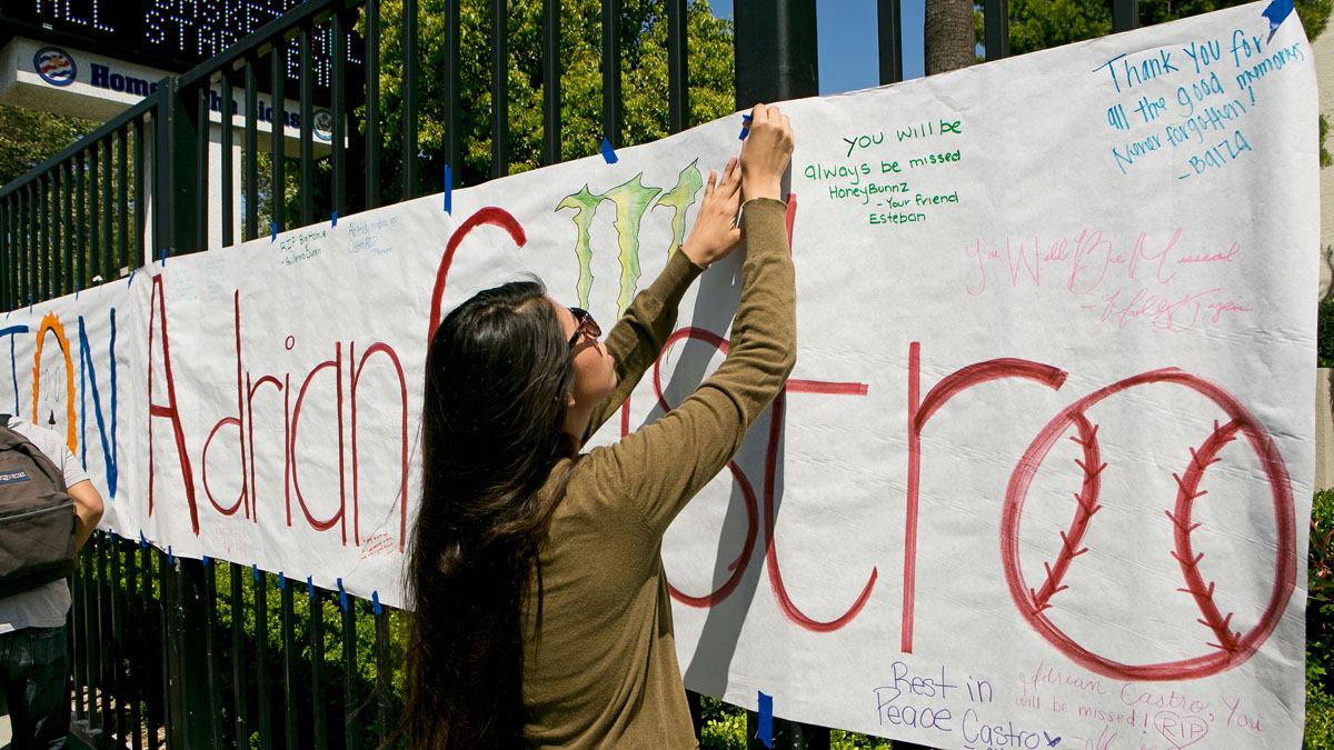 An El Monte High School student hangs a banner for senior Adrian Castro, outside El Monte High School in El Monte, Calif., Friday, April 11, 2014. Castro was killed when the Humboldt State University-bound bus he was on crashed in Orland on Thursday, an El Monte school official said.
