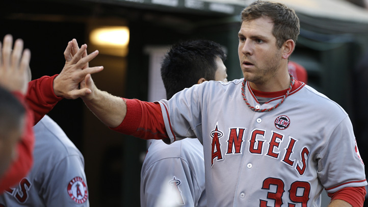 Los Angeles Angels' J.B. Shuck, right, is congratulated after scoring against the Oakland Athletics in the third inning of a baseball game on Thursday, July 25, 2013, in Oakland, Calif. Shuck scored on a single by Angels' Albert Pujols.