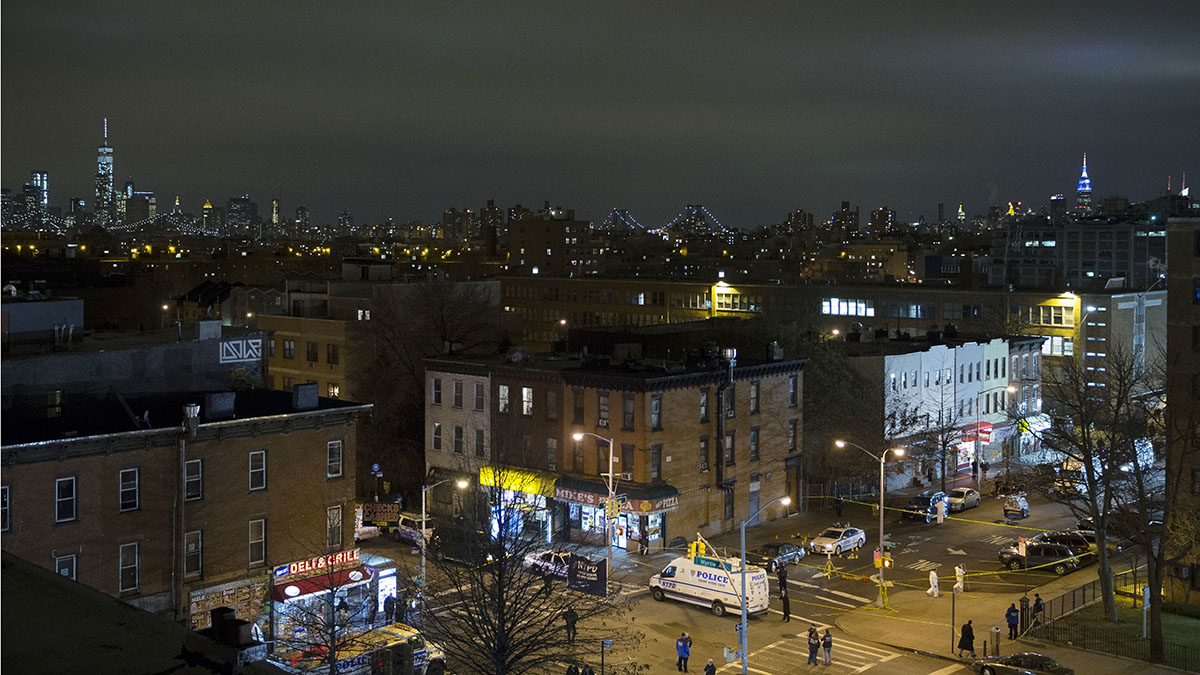 The skyline of Manhattan is seen in the background as investigators work at the scene where two NYPD officers were shot, Saturday, Dec. 20, 2014 in the Bedford-Stuyvesant neighborhood of the Brooklyn borough of New York.