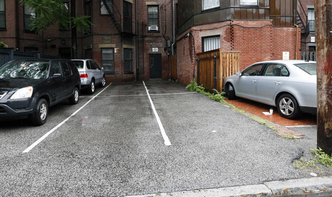 Parking spaces behind 298 Commonwealth Avenue in Boston are seen Friday, June 14, 2013. The two open spaces at right, front and back, were sold at auction on Thursday for $560,000. (AP Photo/Michael Dwyer)
