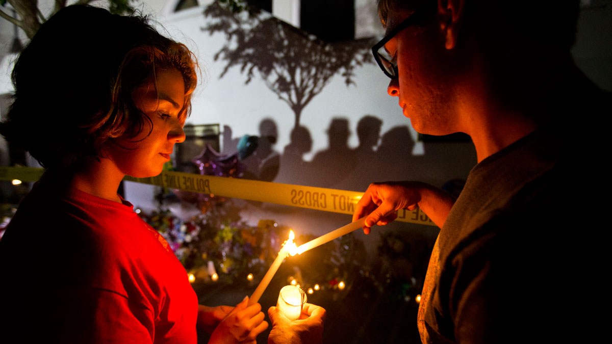 Olina Ortega, left, and Austin Gibbs light candles at a memorial in front of Emanuel AME Church in Charleston, S.C., June 18, 2015.