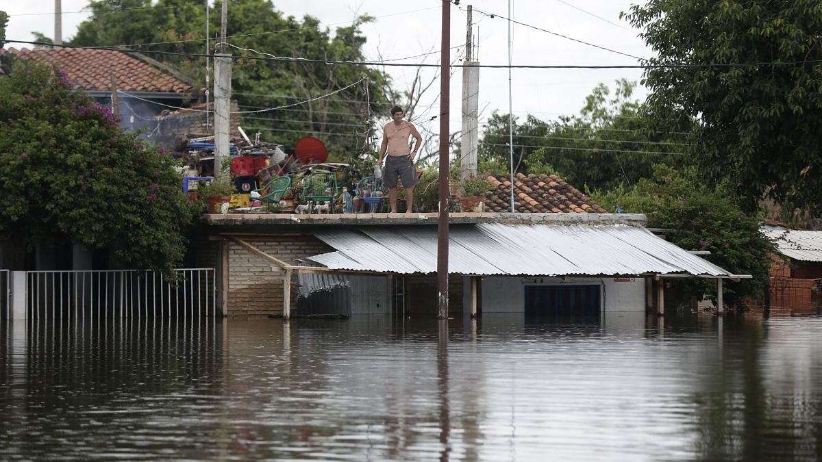 A man observes the water from the roof of his home in a flooded neighborhood in Asuncion, Paraguay, Sunday, Dec. 27, 2015. Widespread floods have forced nearly 140,000 people from their homes in Paraguay, Argentina, Uruguay and Brazil following days of torrential rains that drenched a region where the countries border each other. (AP Photo/Jorge Saenz)