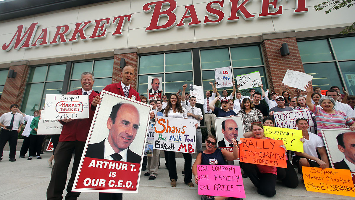 Market Basket assistant managers Mike Forsyth, left, and John Surprenant, second from left, hold signs while posing with employees in Haverhill, Mass., Thursday, July 24, 2014, in a show of support for