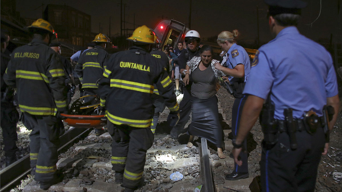 Emergency personnel help passengers at the scene of a train wreck, Tuesday, May 12, 2015, in Philadelphia. An Amtrak train headed to New York City derailed and crashed in Philadelphia.