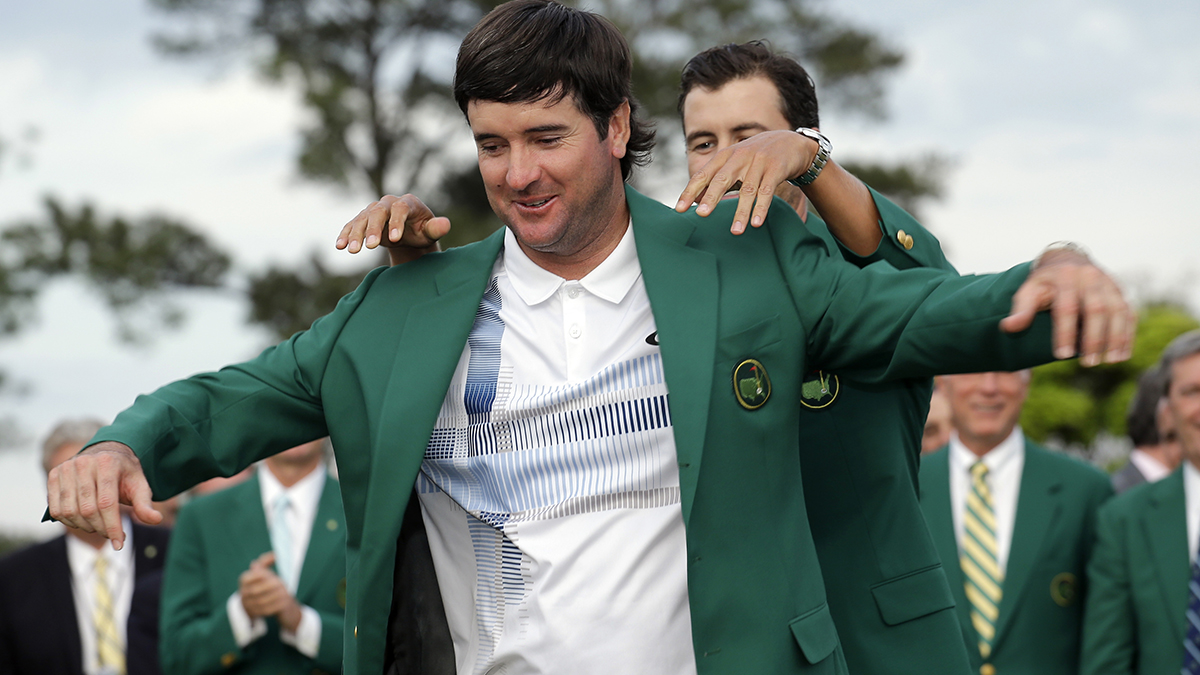 Defending Masters' champion Adam Scott, of Australia, helps Bubba Watson, left, with his green jacket after winning the Masters golf tournament Sunday, April 13, 2014, in Augusta, Ga.