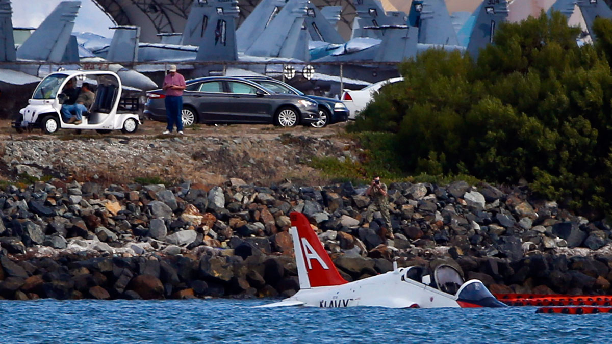 A US Navy aircraft sits in shallow water in San Diego Bay after over shooting a runway at the North Island Naval Station Friday, May 22, 2015 in San Diego. The pilot ejected and was reportedly picked up by a civilian craft.