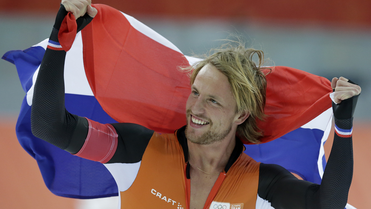Michel Mulder from the Netherlands holds his national flag and celebrates winning gold in the men's 500-meter speedskating race during the 2014 Winter Olympics, Monday, Feb. 10, 2014.