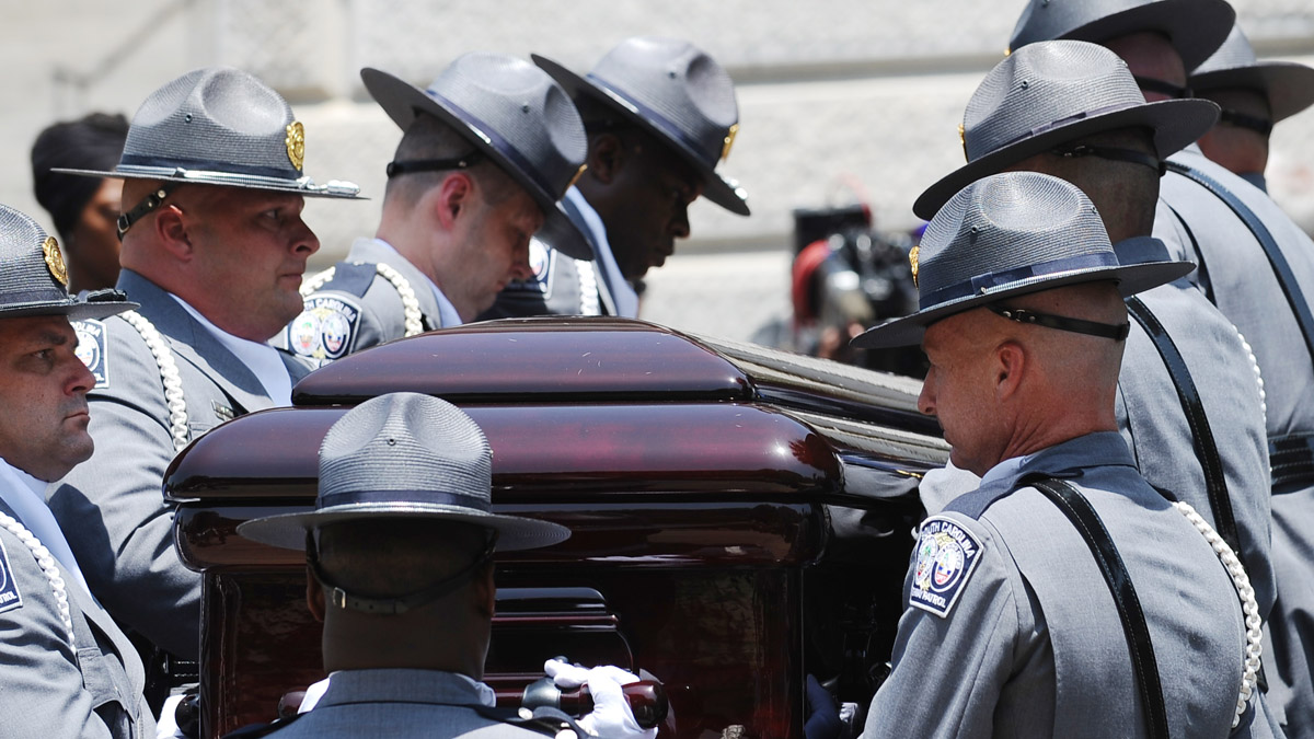 A South Carolina Highway Patrol honor guard carries Sen. Clementa Pinckney's casket to the Statehouse, Wednesday, June 24, 2015, in Columbia, S.C. Pinckney's open coffin was being put on display under the dome where he served the state for nearly 20 years. Pinckney was one of those killed in a mass shooting at the Emanuel AME Church in Charleston.