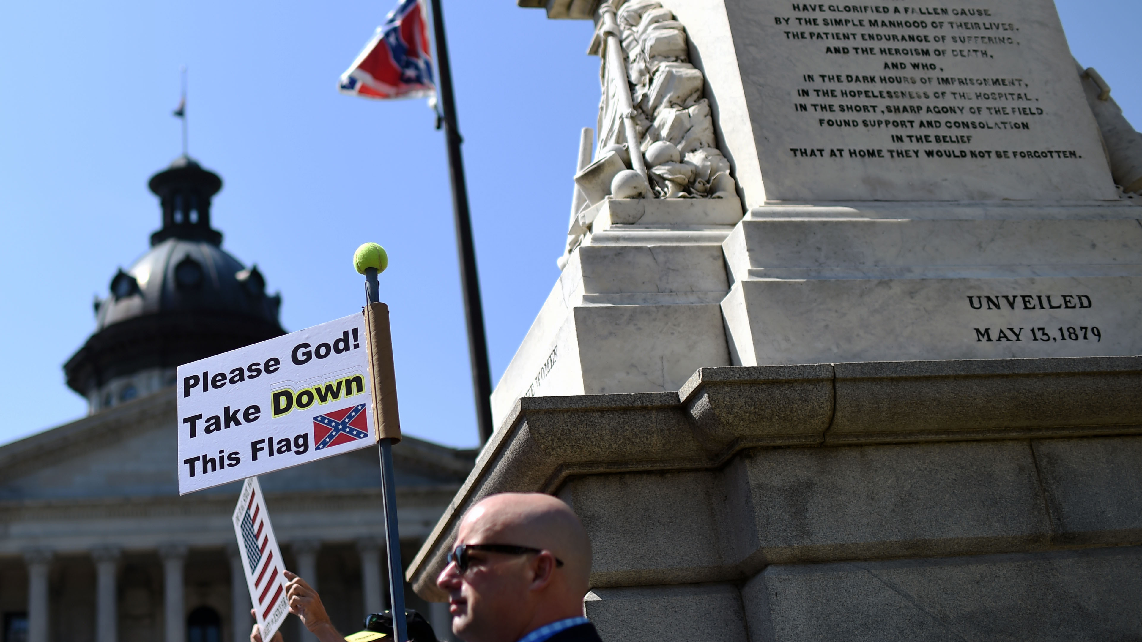 A Columbia, South Carolina, man demands the Confederate flag be removed from the State House grounds at a rally Tuesday. The shooting deaths of nine people at a black church in Charleston have reignited calls for the Confederate flag flying at the State House to come down.