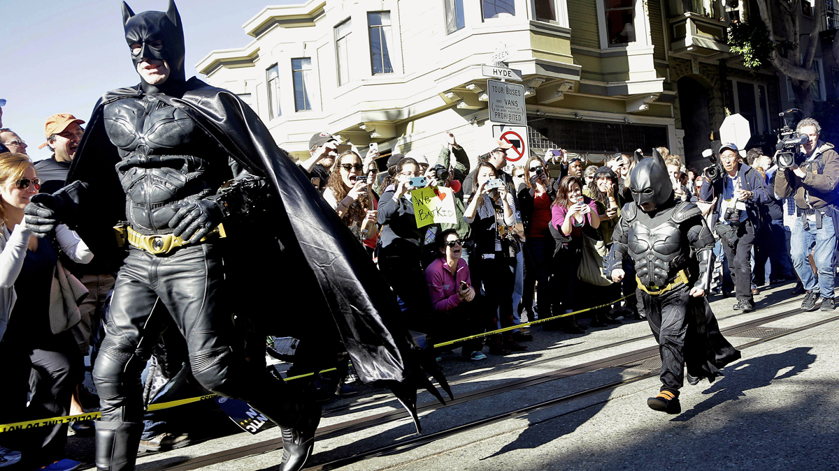 Miles Scott, dressed as Batkid, right, runs with Batman after saving a damsel in distress in San Francisco, Friday, Nov. 15, 2013. San Francisco turned into Gotham City on Friday, as city officials helped fulfill Scott's wish to be