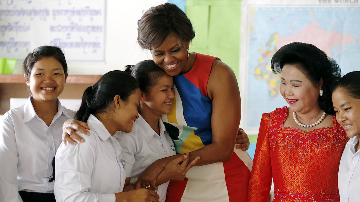 Michelle Obama, center, hugs students at a local high school that she visited with Bun Rany, the first lady of Cambodia, second right, Saturday, March 21, 2015, on the outskirts of Siem Reap, Cambodia as she promote the education initiative