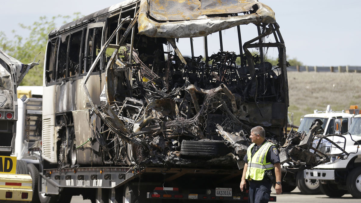A California Highway Patrol officer walks past the charred remains of a tour bus at a CalTrans maintenance station in Willows, Calif., Friday, April 11, 2014. At least ten people were killed and dozens injured in the fiery crash on Thursday, April 10, between a FedEx truck and a bus carrying high school students on a visit to a Northern California college.