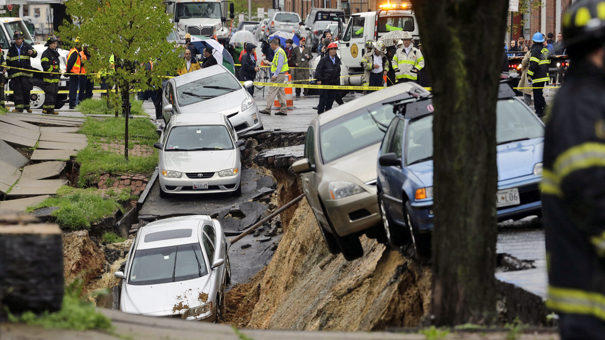 Cars are perched precariously on the edge of a sinkhole that opened up Wednesday, April 30, in the Charles Village neighborhood of Baltimore, as heavy rain moves through the region. Click through to see more of the sinkhole's damage.