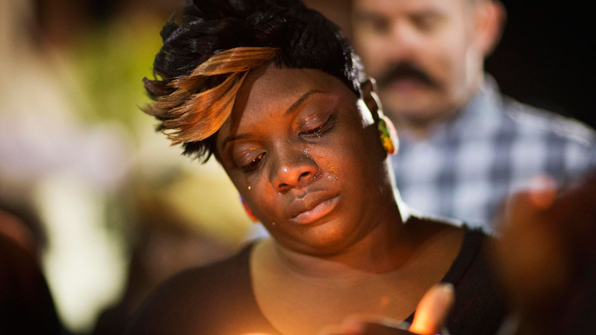 Tears roll down the face of Candice Ancrum, of Summerville, S.C., as she attends a candlelight vigil outside city hall protesting the shooting death of Walter Scott, April 8, 2015, in North Charleston, S.C