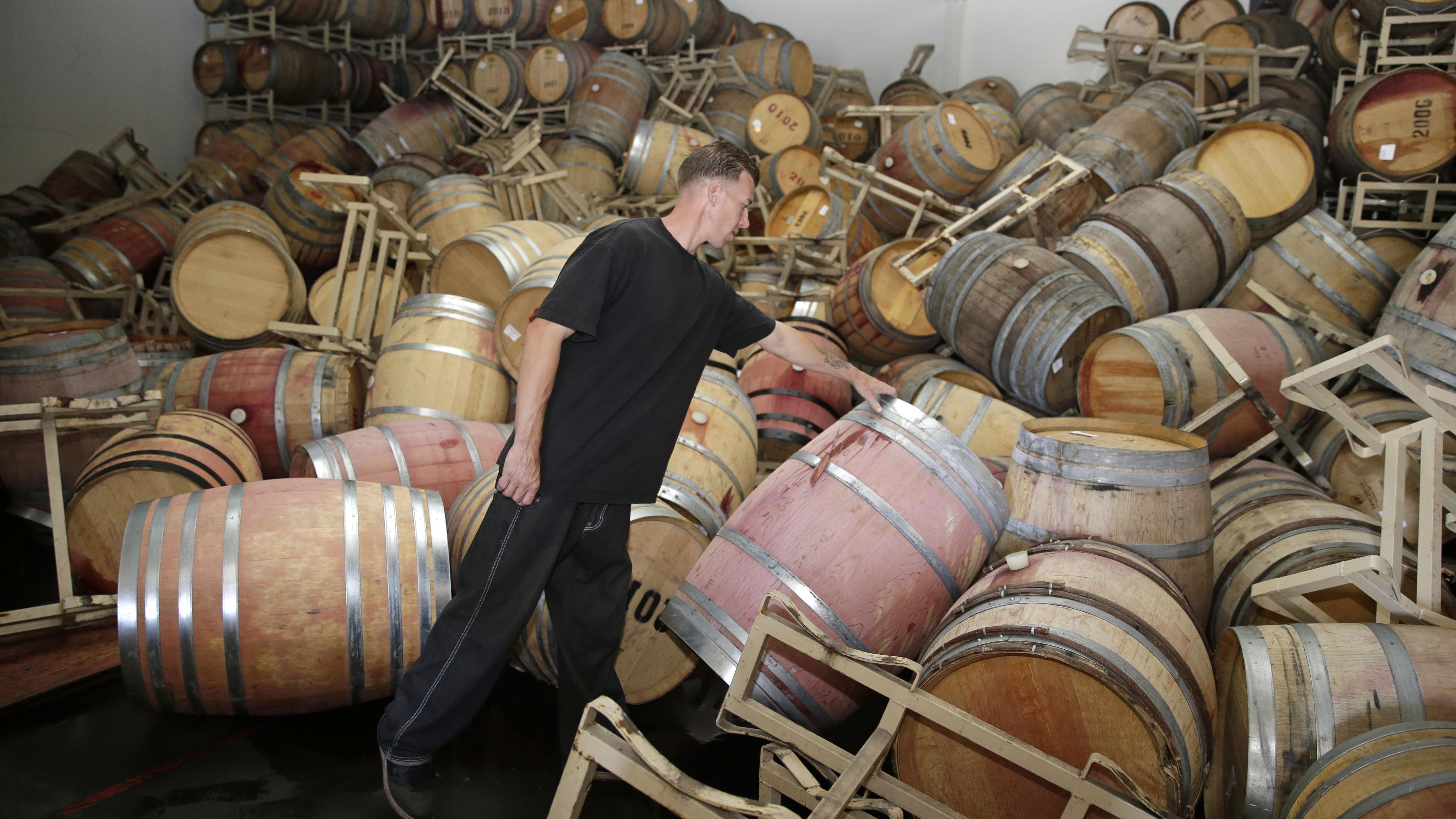 Cellar worker Daniel Nelson looks over toppled barrels of Cabernet Sauvignon following an earthquake at the B.R. Cohn Winery barrel storage facility Sunday, Aug. 24, 2014, in Napa, Calif. Winemakers in California's storied Napa Valley woke up to thousands of broken bottles, barrels and gallons of ruined wine as a result of Sunday's earthquake.  (AP Photo/Eric Risberg)