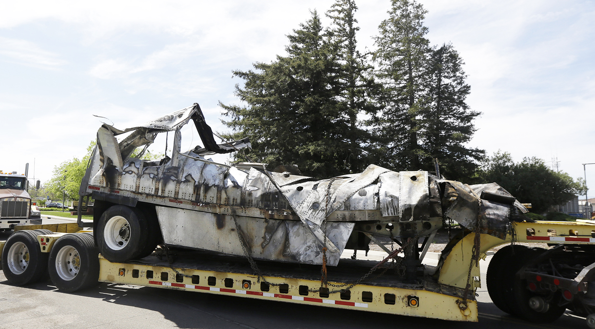 The demolished remains of a FedEx truck is towed into a CalTrans maintenance station in Willows, Calif., Friday, April 11, 2014. At least ten people were killed and dozens injured in the fiery crash on Thursday, April 10, between a FedEx truck and a bus carrying high school students on a visit to a Northern California college. (AP Photo/Jeff Chiu)