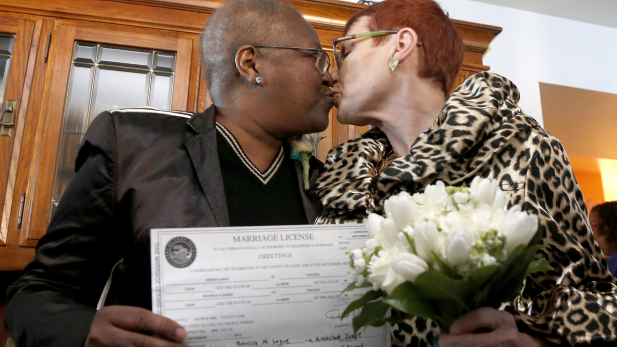 Holding their Illinois marriage license, Vernita Gray, left, and Patricia Ewert kiss after they were married by Cook County Judge Patricia Logue, the first gay marriage in Illinois, at the couple's home Wednesday, Nov. 27, 2013, in Chicago. U.S. District Judge Thomas Durkin on Monday, Nov. 25, 2013, ordered the Cook County clerk to issue an expedited marriage license to Gray and Ewert before the state's gay marriage law takes effect in June 2014, because Gray is terminally ill. (AP Photo/Charles Rex Arbogast)