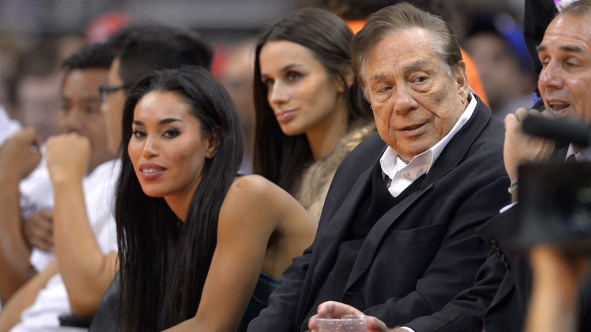 In this photo taken on Friday, Oct. 25, 2013, Los Angeles Clippers owner Donald Sterling, right, and V. Stiviano, left, watch the Clippers play the Sacramento Kings during the first half of an NBA basketball game in Los Angeles. The NBA is investigating a report of an audio recording in which a man purported to be Sterling makes racist remarks while speaking to Stiviano.  NBA spokesman Mike Bass said in a statement Saturday, April 26, 2014, that the league is in the process of authenticating the validity of the recording posted on TMZ's website. Bass called the comments