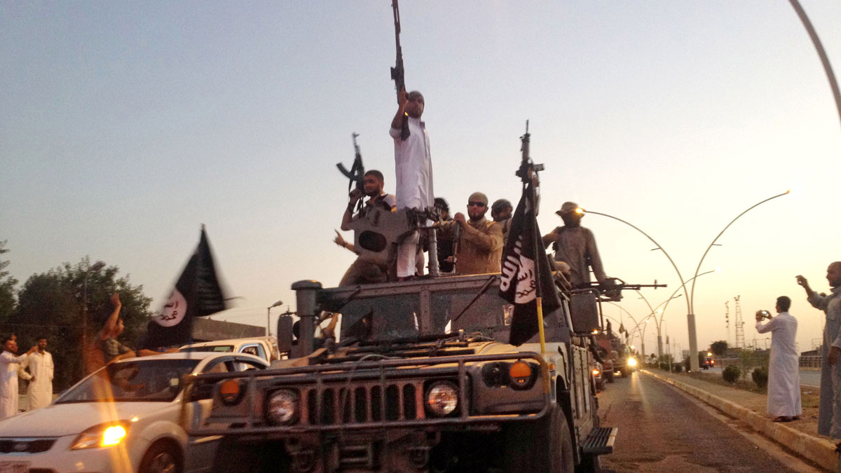 In this June 23, 2014, file photo, fighters from the Islamic State group parade in a commandeered Iraqi security forces armored vehicle down a main road at the northern city of Mosul, Iraq. Abu Bakr Al-Baghdadi's fighters took over Iraq's second-largest city of Mosul in June, 2014, followed by Saddam Hussein's hometown of Tikrit and smaller communities in the Sunni heartland as government forces melt away.